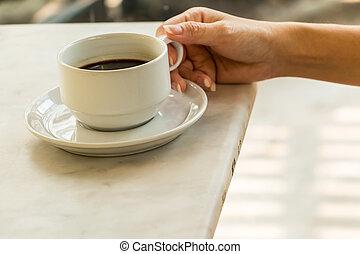 Hand on coffee cup