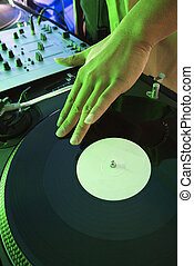 Hand on record. - Close-up of Asian young adult male DJ\'s...