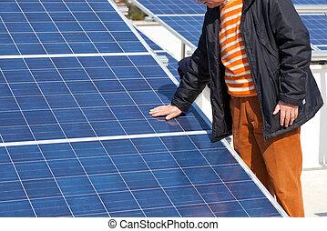 Hand on solar panel