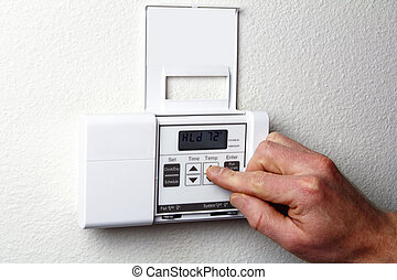 Hand on Thermostat - Fingers pushing control buttons on ...