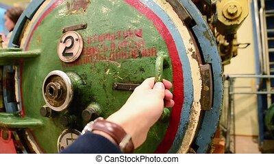 Hand open round iron hatchway of submarine in hall of fleet museum. Exhibit