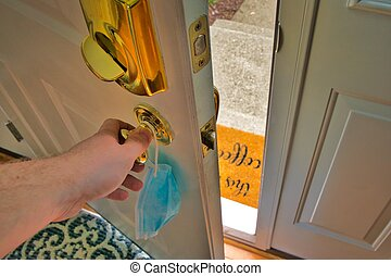 Hand opening door holding a face mask.