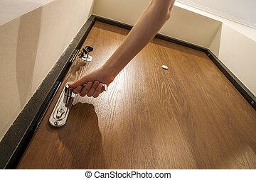 Hand opening the door. Thief or burglar trying to enter a house, break the door. Door handle.