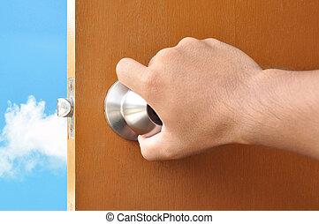 Hand opening the door with sky view behind