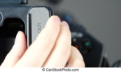 Hand opens audio and video outputs of digital camera, close up