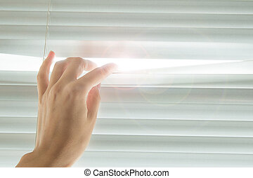 Hand opens the blinds in sunny day
