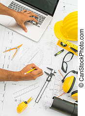 Hand over Construction plans with yellow helmet and drawing tools on blueprints .