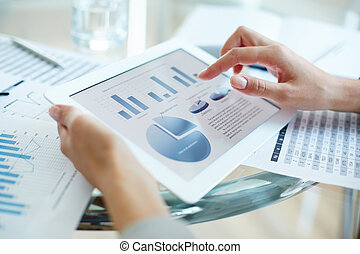 Hand over touchpad - Financial report in touchpad and hand...