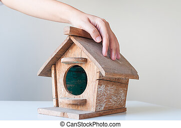Hand over wood bird house. Low budget house concept.