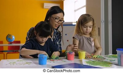 Hand painting activity keeping diverse kids busy - Cheerful...