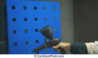 Hand painting of a metal surface by spray gun - Man wearing...