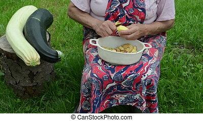 hand peel potato dish - old senior woman hands peel shave...