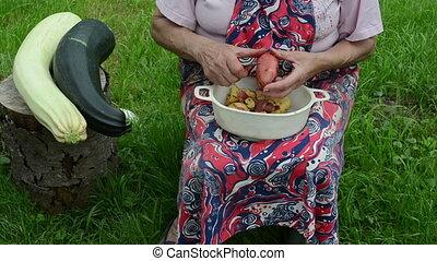 hand peel potato zucchini - old woman with apron hands peel...