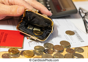 """Hand pensioner, glasses, calculator and wallet with coins on the surface of the table. Translation of the inscription: """"pensioner's Certificate"""""""