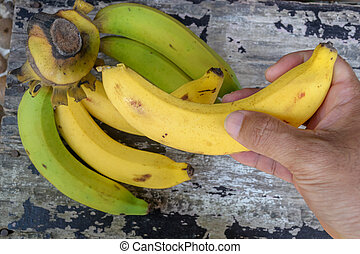 hand picked bananas on wood table.