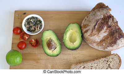 Female hand picking seeds from cutting board with sliced bread, avocado cut in half, lemon, and tomatoes. Avocado toast ingredients from above. Healthy meal preparation