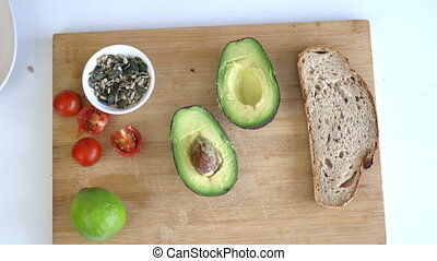 Female hand picking seeds from cutting board with slice of bread, avocado cut in half, lemon, and tomatoes. Avocado toast ingredients from above. Healthy meal preparation