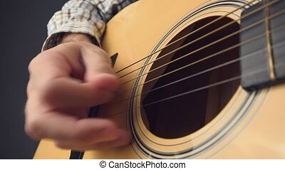 Hand picking strings on acoustic guitar, unplugged blues rock music performance, close up