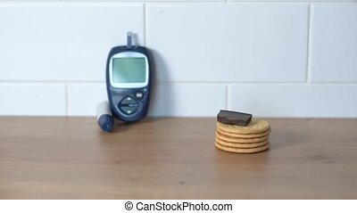 Hand picking sweets on the kitchen table with Glucose meter on the background. Diabetes global problem. Sugar high level