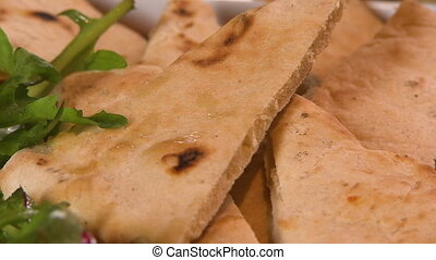 Hand picking up a slice of pita bread - Close up shot of a...