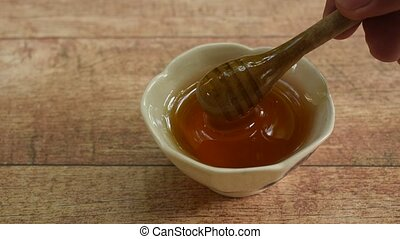 hand picking wooden honey scoop from cup