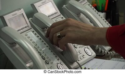 Hand picks up the phone and dials a number on the phone. -...