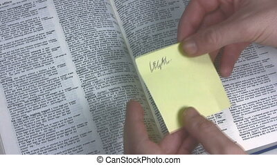 Legal - Hand placing a yellow sticky paper with the word...