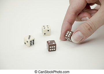 Hand placing dice on white background.