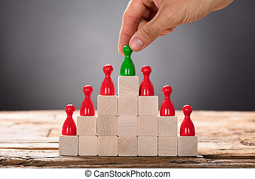 Hand Placing Green Pawn With Other Red Figurines On Blocks -...