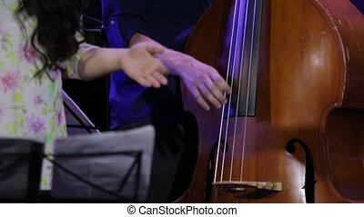 Hand play double bass at a jazz concert closeup
