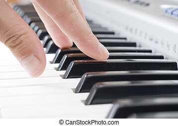 hand playing music on the piano