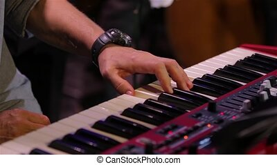 Hand Playing Piano Keyboard - One hand playing red piano...