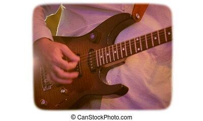 hand plays the electric guitar. 8mm retro style film.