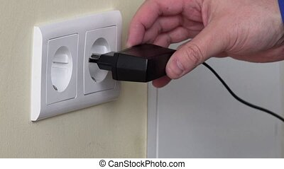 hand plug charger adapter into wall socket. - hand plug...