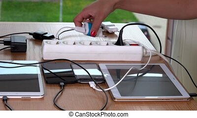 Hand plugging various devices chargers to extension sockets...
