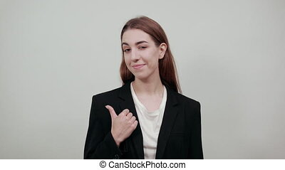 Hand pointer with forefinger pointing aside. Index finger to show direction. Means choosing, introducing too. Indicating towards. Young attractive woman with brown hair in a light t-shirt