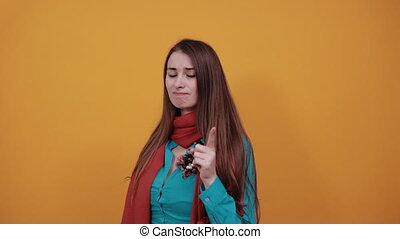 Hand pointer with forefinger pointing forward. Index finger to show direction. Means choosing, introducing too. Indicating towards. Young attractive woman with brown hair, eyes, blue shirt, yellow
