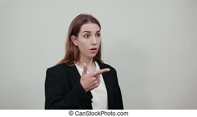 Hand pointer with forefinger pointing forward. Index finger to show direction. Means choosing, introducing too. Indicating towards. Attractive woman with brown hair in a light t-shirt, black jacket