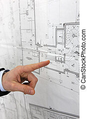 Hand pointing at an architect's diagram