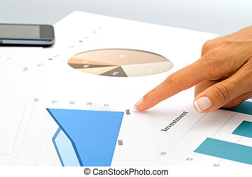 Hand pointing on investment documents.