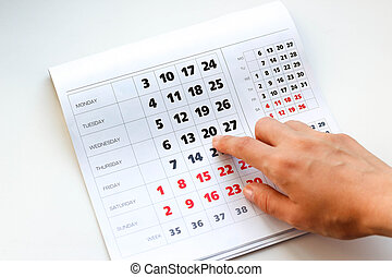Hand pointing to the calendar. White calendar. Weekends are highlighted in red. Close up