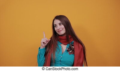 Hand points index finger up, pointing forefinger surprise gift option, great idea. Young attractive woman with brown hair and eyes, decoration on blue shirt, yellow background