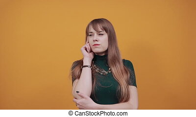 Hand points index finger up, pointing forefinger surprise gift option, great idea. Young attractive woman, dressed green shirt blonde hair, yellow background