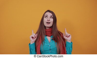 Hand points index fingers up, pointing forefinger surprise gift option, great idea. Young attractive woman with brown hair and eyes, decoration on blue shirt, yellow background