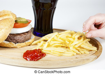 Hand poised to take french fries from a plate also...