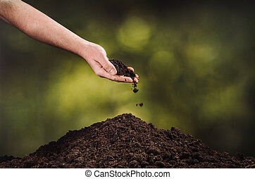Hand pouring black soil on green plant bokeh background -...