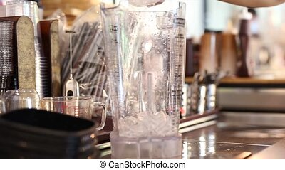 Hand pouring ice cubes in a blender.