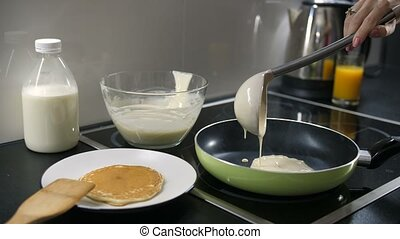 Hand pouring pancake batter into the pan - Close-up of...