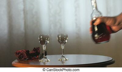 Hand pours a liqueur in wine glasses from a carafe