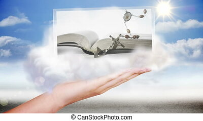 Hand presenting religion and bible clips on blue sky...